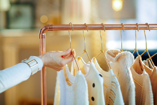 Closeup on stylish woman taking sweaters on hanger from rack