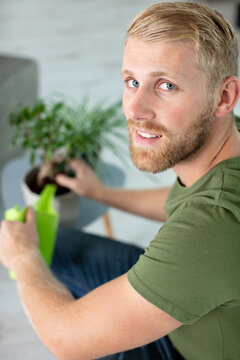 a man is watering and spraying home plants