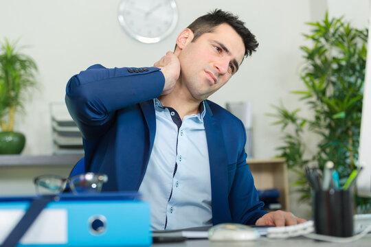 male office worker having stiff neck