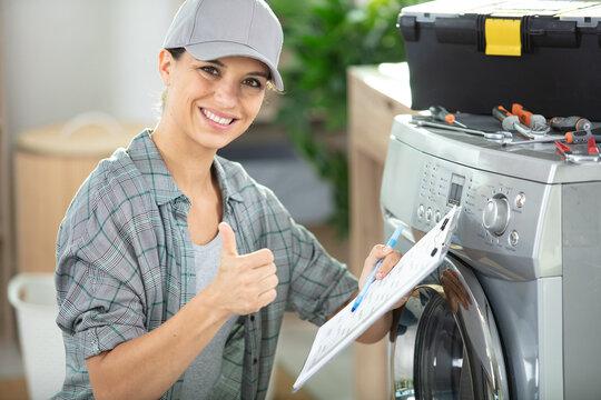 young woman repairing washing machine