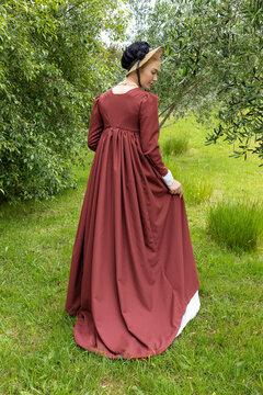 A Regency woman walking alone in a garden wearing a red spencer and a bonnet