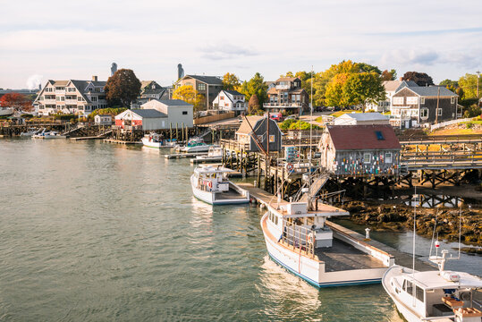 View of a fishing harbour with boats moored to wooden piers at sunset in autumn. Residential buildings are visible in background. Kittery, ME, USA.