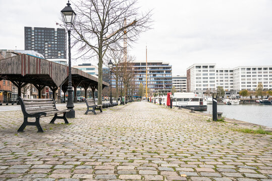 Cobbled footpath lined with benches, street lights and trees alongside a harbour on a cloudy winter day. Some apartment buildings are visible in background. Antwerp, Belgium.