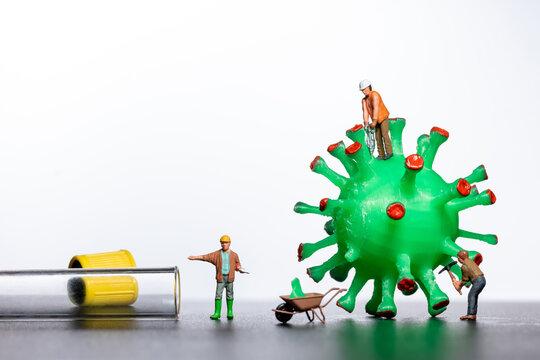 Miniature workers take a sample from a viral model, on a white background close-up. Taking an analysis For the covid-19 test. Miniature models of people destroy and investigate the virus.