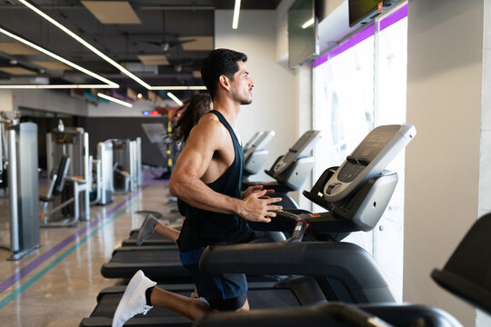 Profile of a fit latin man running on a treadmill