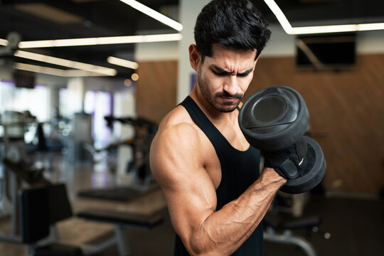 Strong young man flexing his biceps in the gym