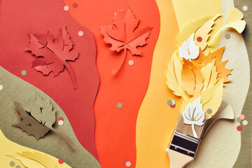Brush loaded with paint made from paper Autumn leaves. Home renovation concept background, top view.