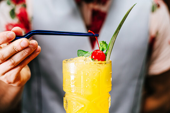 Bartender putting a cherry on a tiki cocktail