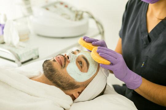 Limpieza facial de un hombre calvo en un spa, con fondo blanco y guantes morados