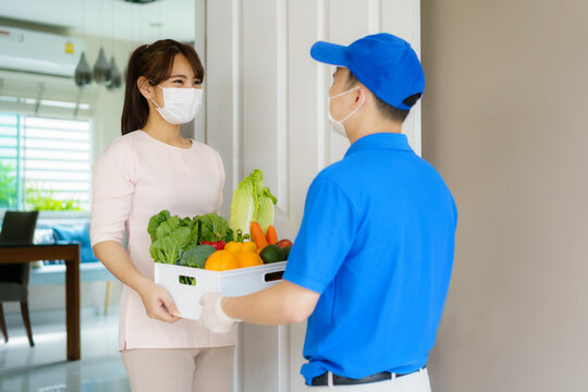 Asian woman costumer wearing face mask receive groceries box of food, fruit and vegetable from delivery man   in front of the house during time of home isolation.