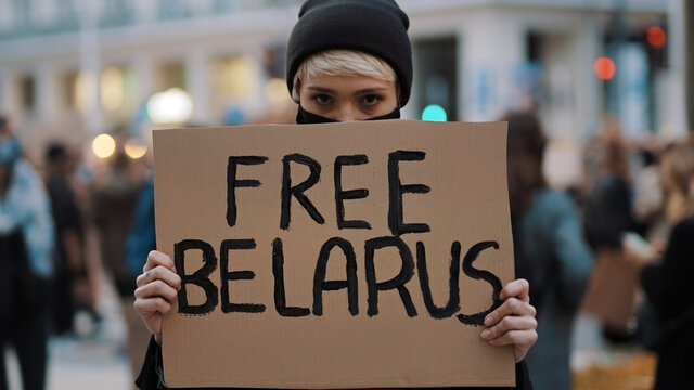 Young woman with face mask holding banner with writtings - free belarus. High quality photo