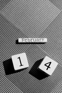 White wooden blocks showing the date of Valentine's day, 14th February, on a silver metallic background