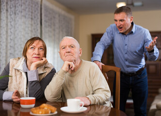 Adult annoyed man scolding his senior parents at home