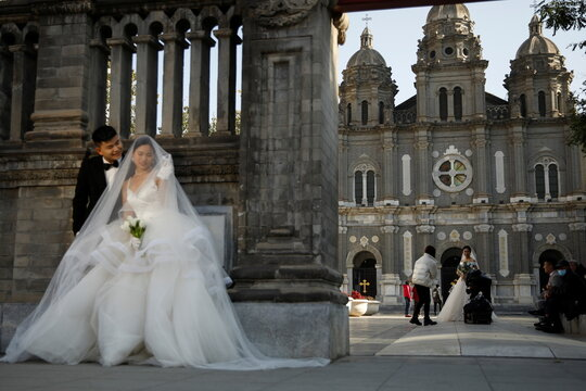 Couples attend their wedding photos shootings in front of the St. Joseph's Catholic Church in Beijing