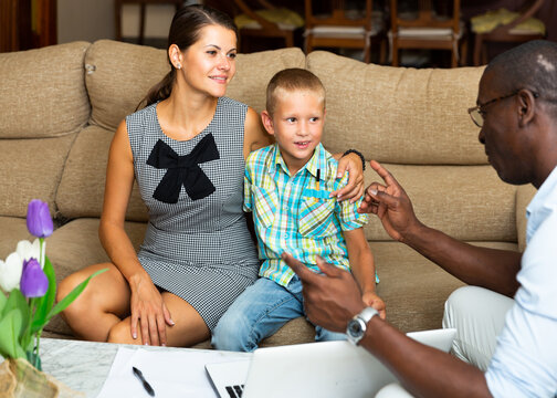 Woman and preschool son meeting with male teacher at home