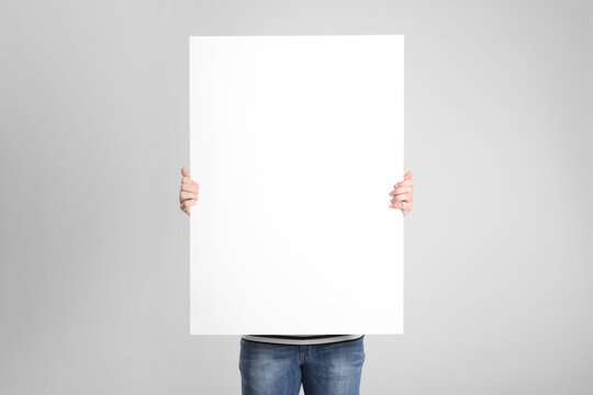 Man holding blank poster on light grey background