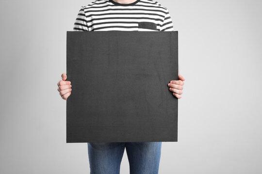 Man holding blank poster on light grey background, closeup