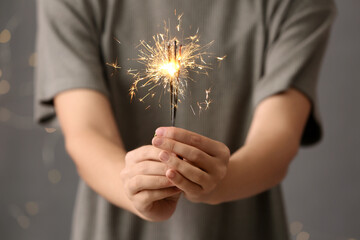 Woman holding burning sparklers against blurred lights, closeup