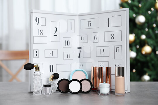 Christmas advent calendar with perfumes, skin care and decorative cosmetics on table