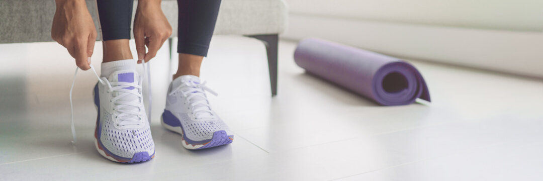 Home workout woman getting ready for training tying her purple running shoes and yoga mat banner panoramic. Fitness during coronavirus, active sport.