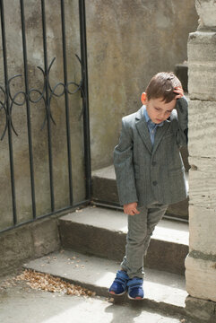 Sad little boy on the background of an old wall and stairs with a gate
