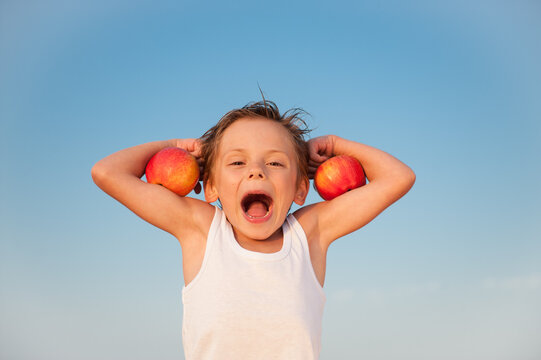 funny kid in white tank top with red apples on biceps muscle on blue sky background with copy space