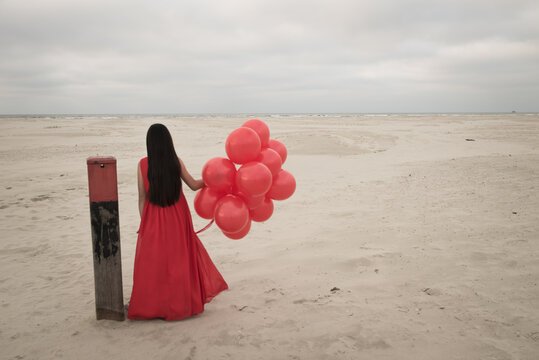 Girl standing on beach in classic red dress holding bunch of red balloons