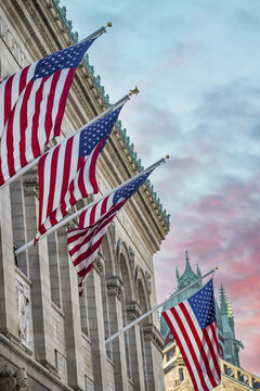 American Flags hanging from a old city building at sunset