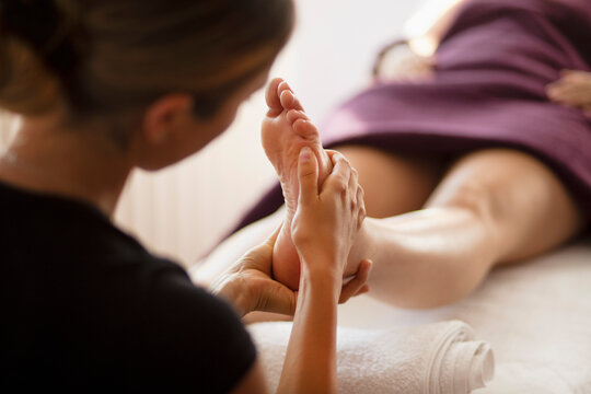 Close up female masseuse massaging client's foot in spa