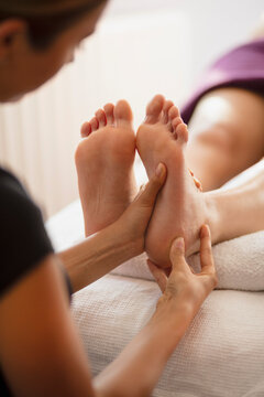 Female masseuse massaging client's foot in spa