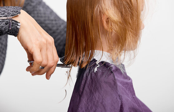 Hair cutting process. Beautiful little girl at the barber shop, hairdresser making a hair style to cute caucasian 4-5 year old little girl