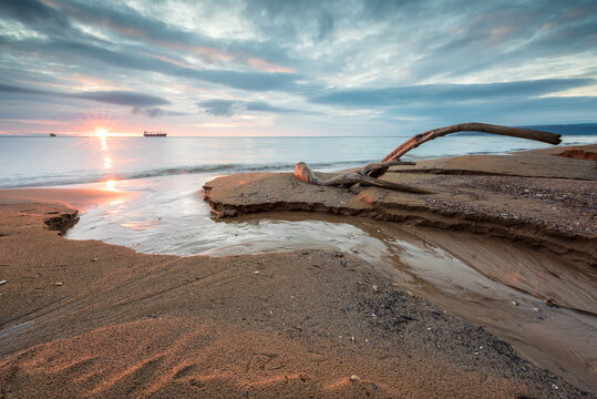Magnificent long exposure sunrise view with a log at the Black Sea coast, Bulgaria