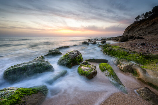 Amazing long exposure seascape with rocky beach at sunrise