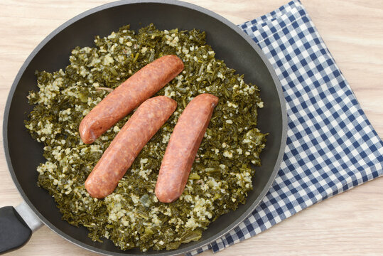 Fresh cooked kale with sausages on wooden table