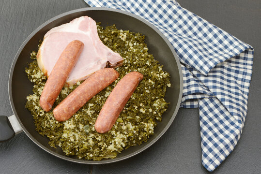 Fresh cooked kale with sausages and meat  in the pan on black background