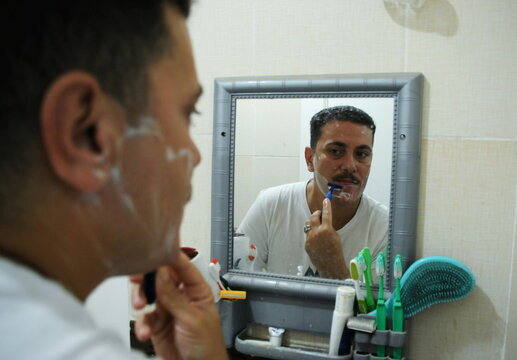 Egyptian transgender man Mohamed Fathallah looks at his reflection in the mirror while shaving at his home in Cairo
