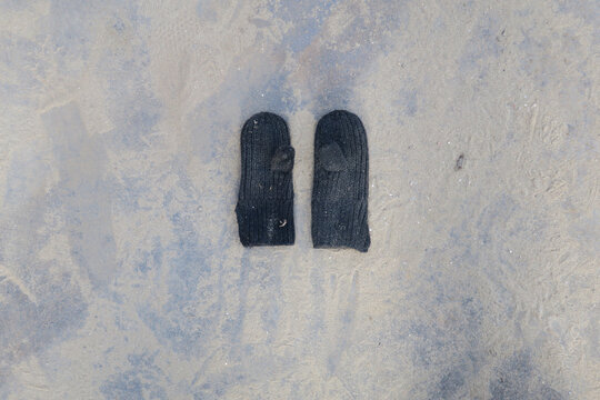two little black gloves laying on a sandy metal plate