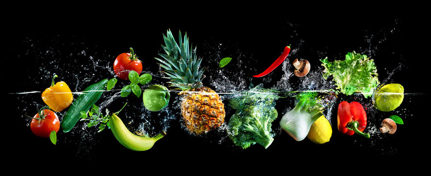 Fresh vegetables, fruits and water splashes on panoramic background