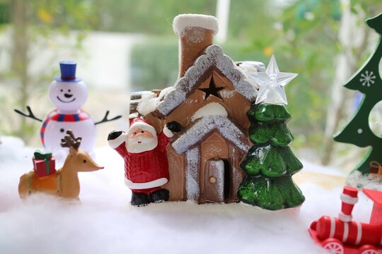Santa Claus and wooden house with christmas tree, reindeer carrying red gift box, and snowman on snowy background. Christmas display and toy concept.