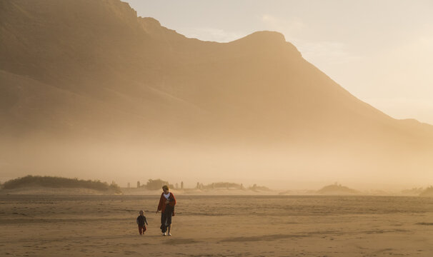 Silhouette of a young mother walking with her little child on a summer day in Cofete, Fuerteventura, Canary Islands, Spain.