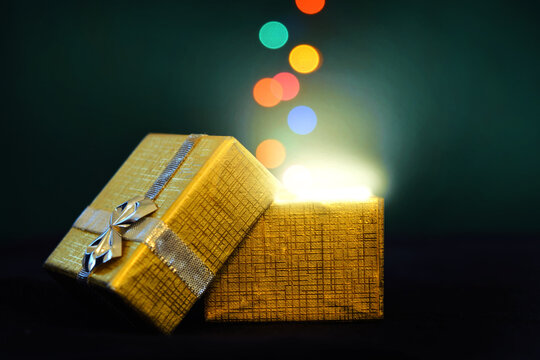 An opened Christmas present box with ribbon and gold wrapping. Lid is open with glowing white light shining out of the box. Colorful orbs of light appear to float upward out of the gift box.