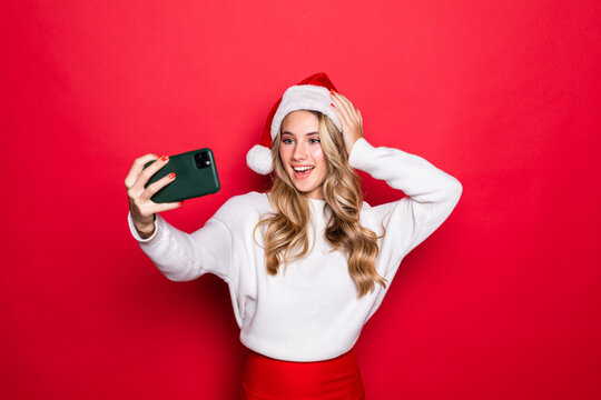 Portrait of a pretty woman wearing Christmas hat taking a selfie isolated over red background
