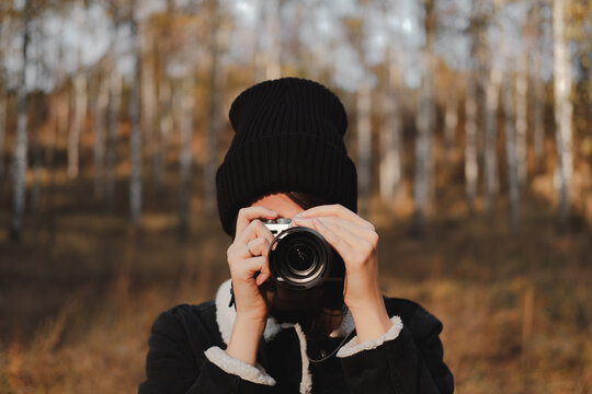 Portrait of a young woman with camera taking a picture in beauti