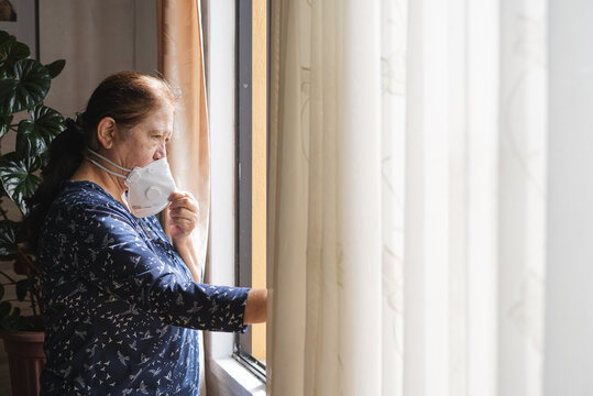 Woman in home during quarantine looking the outside throughthe window