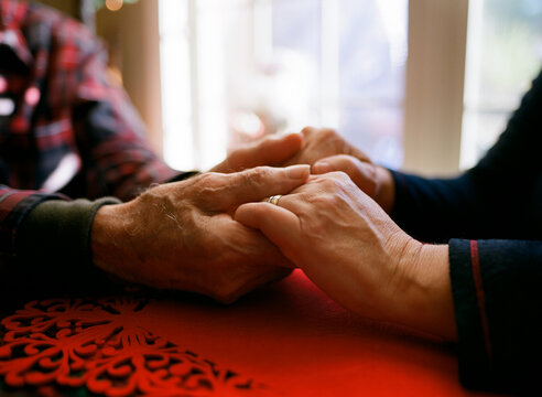 Father holding daughter's aged hands. Comforting warming old age