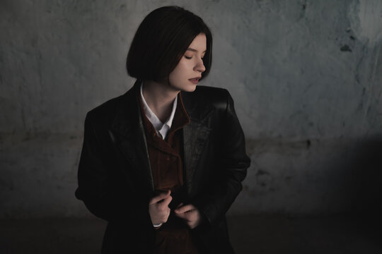 Young woman in leather jacket, low key portrait, grunge backgrou