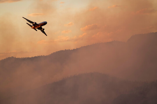 Military aircraft flying over smoke emitting from wildfire in forest during sunset