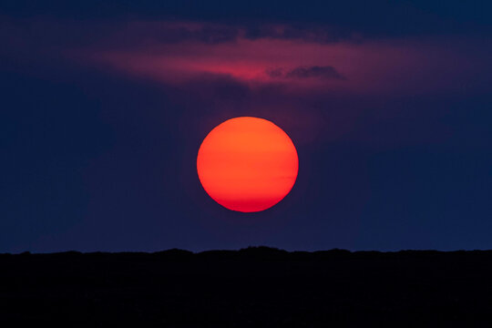 Idyllic shot of orange moon over silhouette landscape