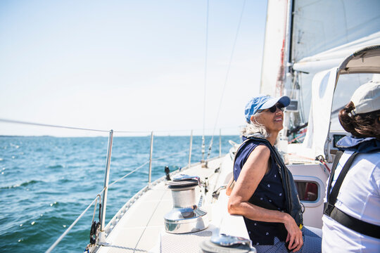 Middle aged woman enjoying family sail on sunny summer day