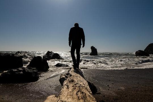 Person walking on large driftwood log toward waves at edge of beach